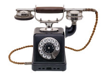 Antique black telephone. Isolated objects: one antique black telephone, very old and aged, isolated on white background Royalty Free Stock Image