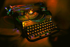 Antique black typewriter. Painted with UV light. Various objects on a dark background.  Artistic blur Stock Photos