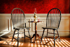 Antique Black Windsor Chairs in Old Historic Home. Antique black distressed Windsor style chairs and mahogany table with glasses and oil lamp in an early Stock Images