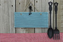 Antique blank blue sign with iron keys, gingham tablecloth and cast iron spoon and fork hanging on wooden background Royalty Free Stock Photography