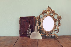Antique blank Victorian style frame and old book with vintage necklace on wooden table. retro filtered image Stock Photos