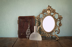 Antique blank Victorian style frame and old book with vintage necklace on wooden table. retro filtered image Royalty Free Stock Photography