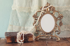Antique blank victorian style frame and old book with vintage pearl necklace on wooden table. retro filtered image Stock Photos