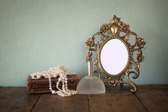 Antique blank Victorian style frame and old book with vintage pearl necklace on wooden table. retro filtered image Stock Photography