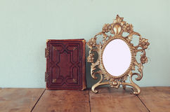 Antique blank victorian style frame and old book on wooden table. retro filtered image. template, ready to put photography Royalty Free Stock Photos