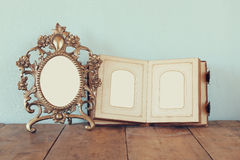 Antique blank victorian style frame and old open photograph album on wooden table. retro filtered image Royalty Free Stock Images