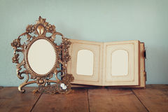 Antique blank victorian style frame and old open photograph album on wooden table. retro filtered image. Royalty Free Stock Images