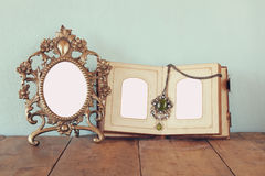 Antique blank victorian style frame and old open photograph album on wooden table. retro filtered image. Stock Photo