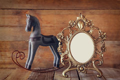 Antique blank victorian style frame and old rocking horse over wooden table Royalty Free Stock Photos