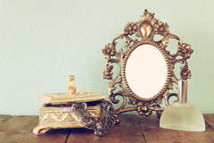 Antique blank victorian style frame, perfume bottle and neckless on wooden table. retro filtered image Stock Photos