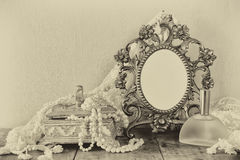 Antique blank victorian style frame, perfume bottle and white pearls on wooden table. black and white style photo Royalty Free Stock Photo