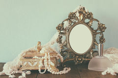 Antique blank victorian style frame, perfume bottle and white pearls on wooden table. retro filtered and toned Stock Photos