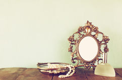 Antique blank victorian style frame, perfume bottle and white pearls on wooden table. retro filtered and toned Royalty Free Stock Image