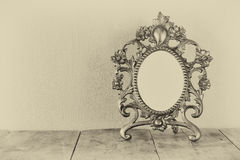 Antique blank victorian style frame on wooden table. black and white style photo. template, ready to put photography.  Royalty Free Stock Image