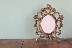 Antique blank victorian style frame on wooden table. retro filtered image. template, ready to put photography Stock Images