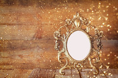 Antique blank victorian style frame on wooden table. vintage filtered image with glitter overlay. template Stock Image