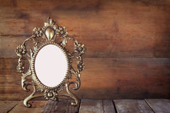 Antique blank victorian style frame on wooden table. vintage filtered image. template, ready to put photography Royalty Free Stock Photos