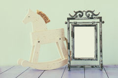Antique blank vintage style frame and old rocking horse over woo Royalty Free Stock Image