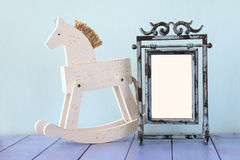 Antique blank vintage style frame and old rocking horse over woo Royalty Free Stock Photos