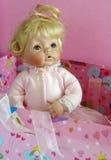 Antique blond porcelain doll portrait. Antique blond porcelain doll on a pink background Stock Photography