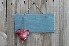Antique blue sign hanging on wood door with gingham heart Royalty Free Stock Image