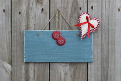 Antique blue sign hanging on wood door with gingham heart and soda pop tops. Antique blank blue sign hanging on wood door with gingham and muslin heart with Stock Photography