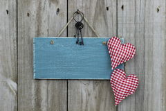Antique blue sign hanging on wood door with hearts and iron keys stock photo