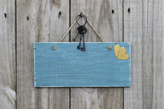Antique blue sign hanging on wood door with hearts and iron keys Royalty Free Stock Photography