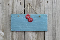 Antique blue sign hanging on wood door with soda pop tops Royalty Free Stock Images
