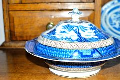 Antique blue and white willow pattern china. On a plate dresser stock images