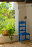 Antique Blue Wooden and Wicker Chair in a Porch. And Sunlit Garden Stock Images