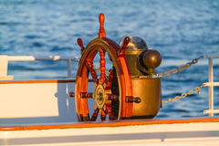 Antique Boat Steering Wheel & Compass. Steering wheel & compass on an old antique sailing boat lit by sunset light Royalty Free Stock Photos