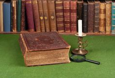 Antique book, candlestick and magnifying glass Royalty Free Stock Images