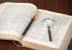 Antique book. Antique dictionary with book knife and lens on it Royalty Free Stock Photography