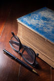 Antique book with eyeglasses and pen. Stock Images