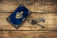 Antique book and old keys over rustic wooden background Stock Images