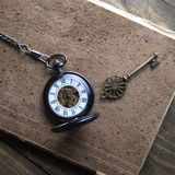 Antique book and pocket watch on grunge wooden table Royalty Free Stock Photo