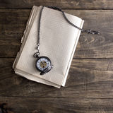 Antique book and pocket watch on grunge wooden table Stock Photo