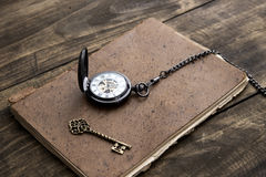 Antique book and pocket watch on grunge wooden table Stock Image