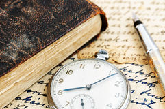 Antique book and pocket watch Stock Photos