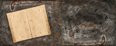 Antique book on rustic metal vintage table surface Royalty Free Stock Photo