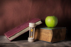 Antique books with apple and hourglass. Stock Photography