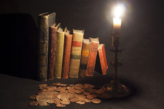 Antique books with coins and candle. Row of antiquarian books illuminated by candle with coins scattered in foreground Royalty Free Stock Photography
