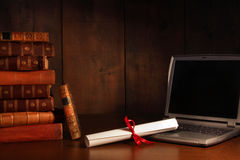 Antique books, diploma with laptop on desk Royalty Free Stock Image