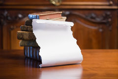 Antique books with empty scroll. Pile of antique books with blank white scroll for copy space Royalty Free Stock Photos