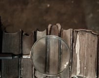 Antique books with magnifying glass. Old leather bound vintage books in a row royalty free stock image