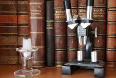 Antique books and microscope. Antique scientific books, a microscope and a glass candle holder stock photography