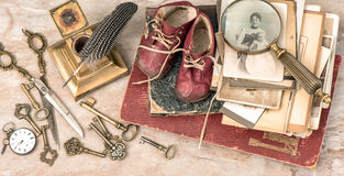 Antique books and photos, keys, baby shoes and writing accessori Royalty Free Stock Photos