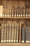 Antique books on shelves. A view of old, antique books on shelves in a wooden bookcase royalty free stock photos