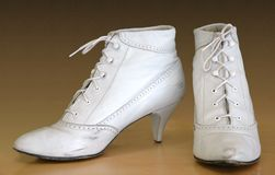 Antique Boots. Early 20th century shoes with round laces. White leather, spike heel Royalty Free Stock Photo